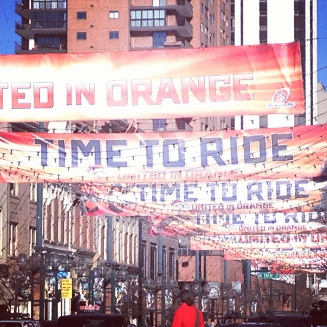 """United in Orange"" and ""Time to Ride"" banners fly high over Larimer Square."